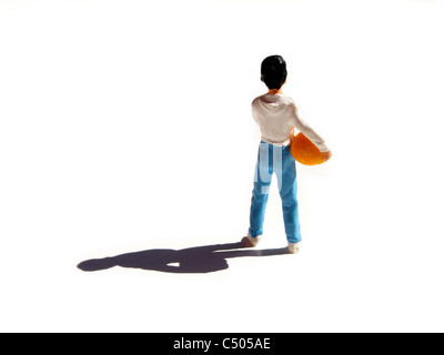 Figurine representing a young boy with a soccer ball under the arm - rear view - Stock Photo