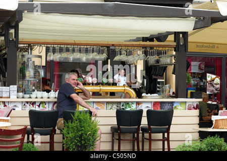 Man sitting at a bar in the Old Market Square, Poznan, Poland - Stock Photo