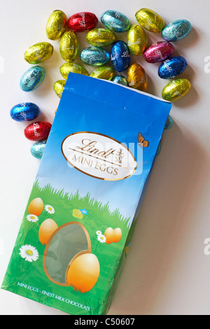 Packet of Lindt mini eggs finest chocolates with foil wrapped eggs spilled on white background - ready for Easter - Stock Photo