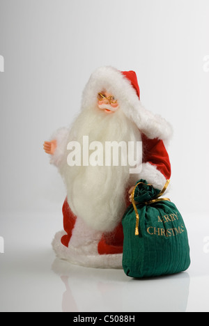 Santa Claus carrying a sack full of presents. - Stock Photo