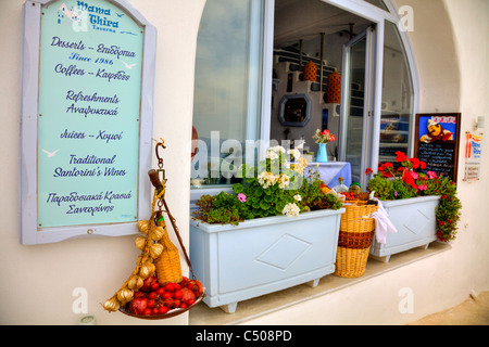 Santorini typical iconic Greek Island restaurant in thira flower box food and menu outside - Stock Photo