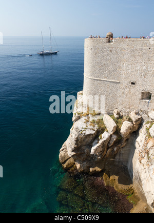 white strong city walls with lookout tower built on rocky shore of Dubrovnik, Croatia - Stock Photo