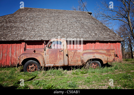 Old rusted truck sitting in front of old red barn in Iowa. - Stock Photo