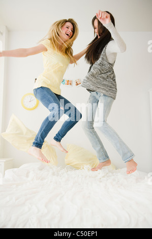 Teenage girls jumping on bed together - Stock Photo