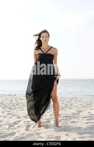 Young woman, 20+, standing in a long dress on the beach, lifestyle, sensuality, space, lightness - Stock Photo