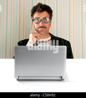 Nerd pensive man with myopic glasses and silly expression in front a laptop computer - Stock Photo