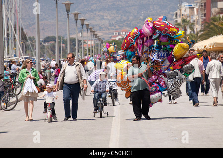 balloon vendor and kids on bicycles on the harbour promenade of the coastal port city Volos, Thessaly, Greece - Stock Photo