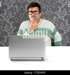 Nerd pensive man with glasses and silly expression in front a laptop computer looking for solution - Stock Photo