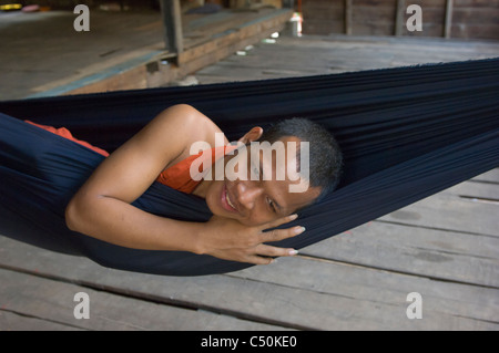 Novice Buddhist monk in a hammock, Wat Lolei, near Siem Reap, Cambodia - Stock Photo