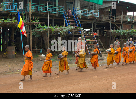 Buddhist monks on their morning alms round, Kompong Klang, on the shore of Tonle Sap lake, near Siem Reap, Cambodia - Stock Photo