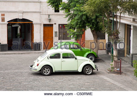 Two green Volkswagen Beetles parked side-by-side in Arequipa, Peru. - Stock Photo