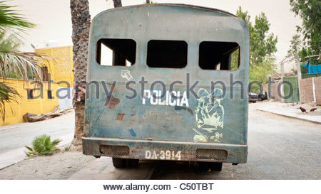 An old police bus with graffiti showing two police officers kissing, Huacachina, Ica Department, Peru - Stock Photo