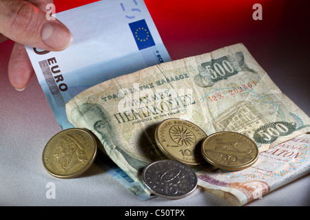 A hand pulling a euro note out from under a pile of Greek drachmas: out with the new, in with the old. - Stock Photo