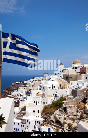 Santorini typical iconic Greek Island blue and white Greek flag flying in the wind at Oia town - Stock Photo