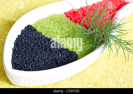 caviar in a bowl-shaped over on yellow background - Stock Photo
