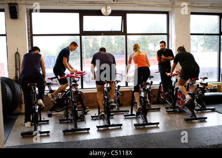 spinning class on stationary bikes in a gym - Stock Photo