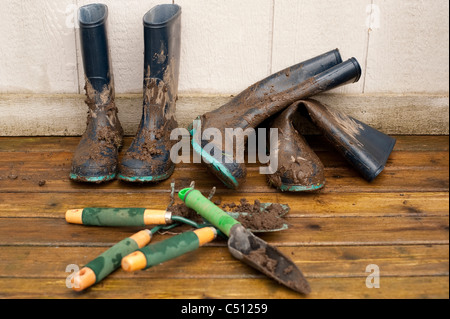 Muddy boots and gardening tools on back deck after working in garden. - Stock Photo