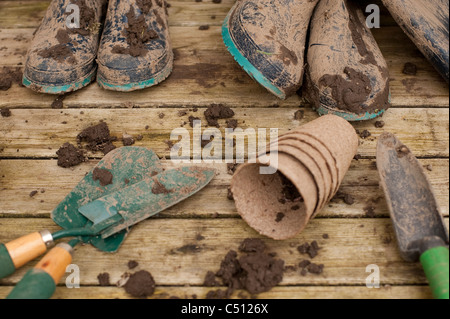 Muddy boots and gardening tools on back deck with flower pots with hyacinth bulb in pot after working in garden. - Stock Photo