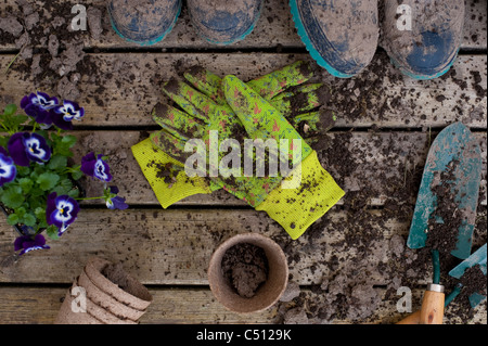 Gardening tools with muddy boots on a back deck with work gloves - Stock Photo