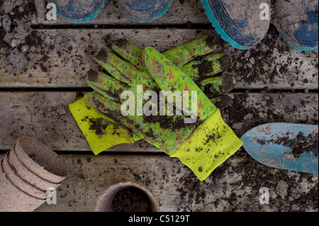 Gardening tools with muddy boots and gardening tools on a back deck with work gloves - Stock Photo