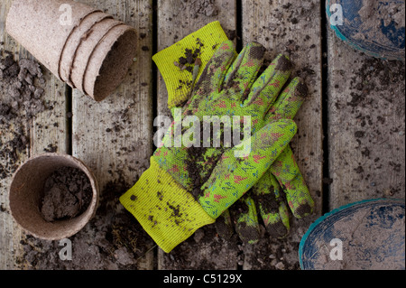 Gardening pots with muddy boots on a back deck with work gloves - Stock Photo