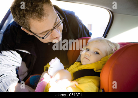Father securing baby girl in car seat - Stock Photo