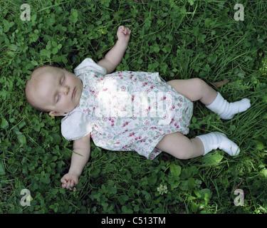 Baby sleeping on grass - Stock Photo