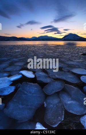Ice flakes drifting towards the mountains on Tjeldoya Island, Norway. - Stock Photo
