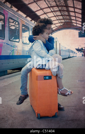 Brother and sister sitting together on suitcase waiting in train station - Stock Photo