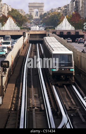 Subway train running on rail track in city, Arc de Triomphe in background - Stock Photo