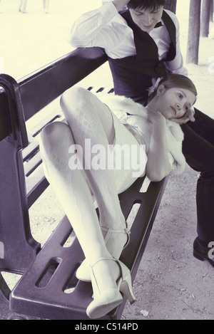 Woman lying on park bench, resting head on boyfriend's lap - Stock Photo