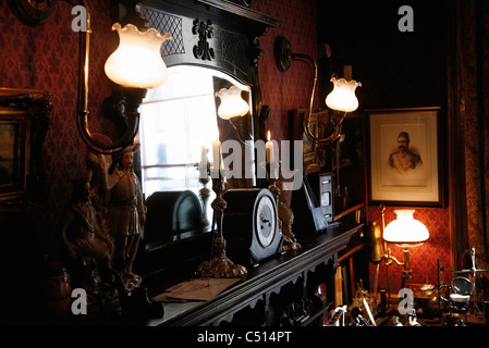 Candles and mirror on mantelpiece - Stock Photo