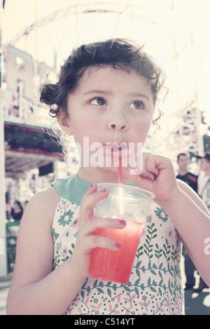 Little girl drinking juice at fair - Stock Photo