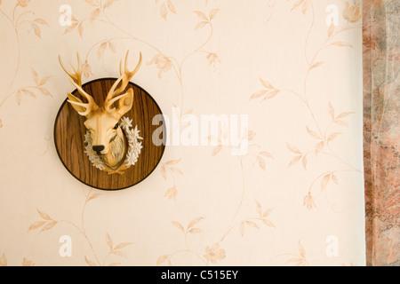 Plastic deer head mounted on wall - Stock Photo