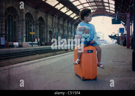 Little girl sitting on suitcase waiting in train station - Stock Photo