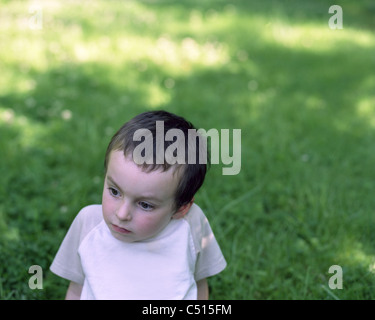 Little boy sitting in grass, looking away in thought - Stock Photo
