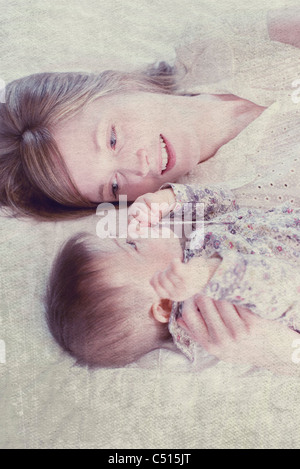 Mother and baby daughter lying side by side, mother looking at baby affectionately - Stock Photo