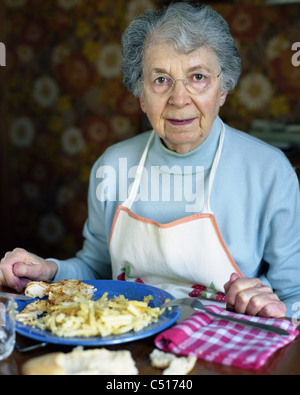Senior woman eating at table, portrait