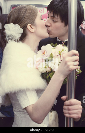 Bride and groom kissing on subway train - Stock Photo