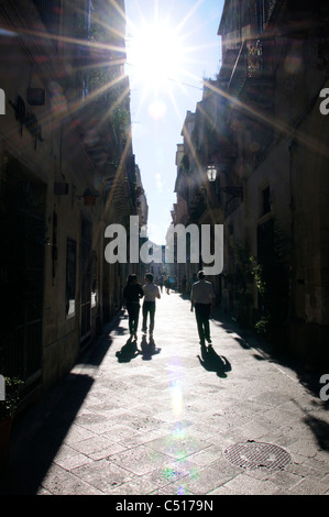 Silhouetted tourists walking in street, Lecce, Puglia, Italy - Stock Photo