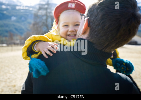 Father carrying baby girl, baby girl smiling - Stock Photo