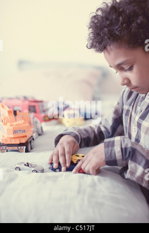 Little boy playing with toy cars - Stock Photo
