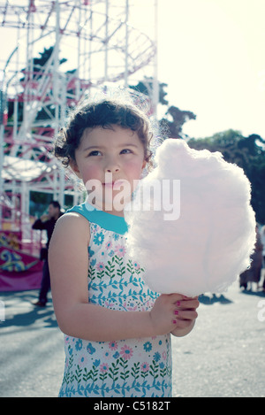 Little girl holding cotton candy at fair, portrait - Stock Photo
