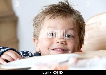 young boy peeking over table - Stock Photo