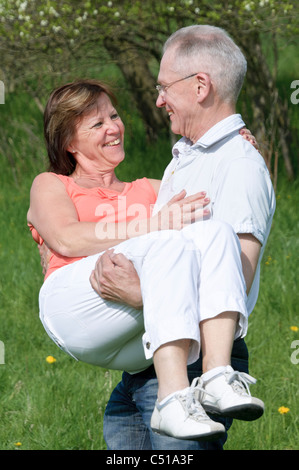 Middle-aged couple, man carrying a woman in his arms - Stock Photo