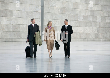 three business people walking through hall - Stock Photo