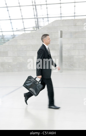 businessman walking through hall - Stock Photo