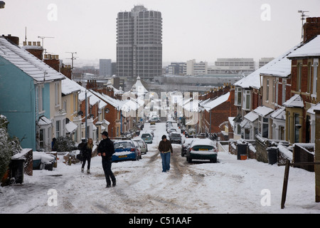 Swindon town centre in the snow, viewed from a side road and at the top of a steep hill - Stock Photo