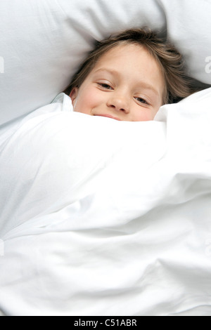 portrait of young girl in bed - Stock Photo