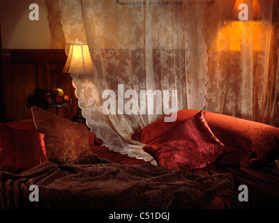 Dimly lit bedroom with dark red bed and two lamps. Interior settings. - Stock Photo